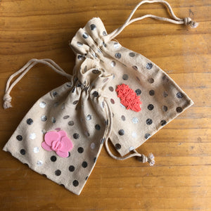 Cotton pouches with silver dots and a coral hyacinth 3D sticker from Styklet on a wood background.