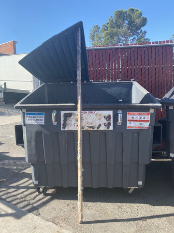 dumpster with lid propped open using wood pole