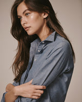 Sideview of a female model wearing the Wingtip Chambray Shirt.