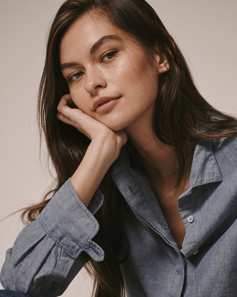 Close-up of a female model wearing the Jonathan Mezibov Wingtip Chambray Shirt with signature tab cuffs.