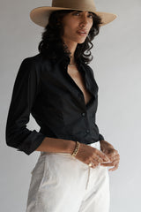 Female model wearing the Lisette Stretch Poplin Shirt, hat and white pants.