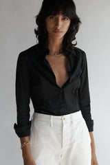 Female model wearing the Lisette Stretch Poplin Shirt and white pants.