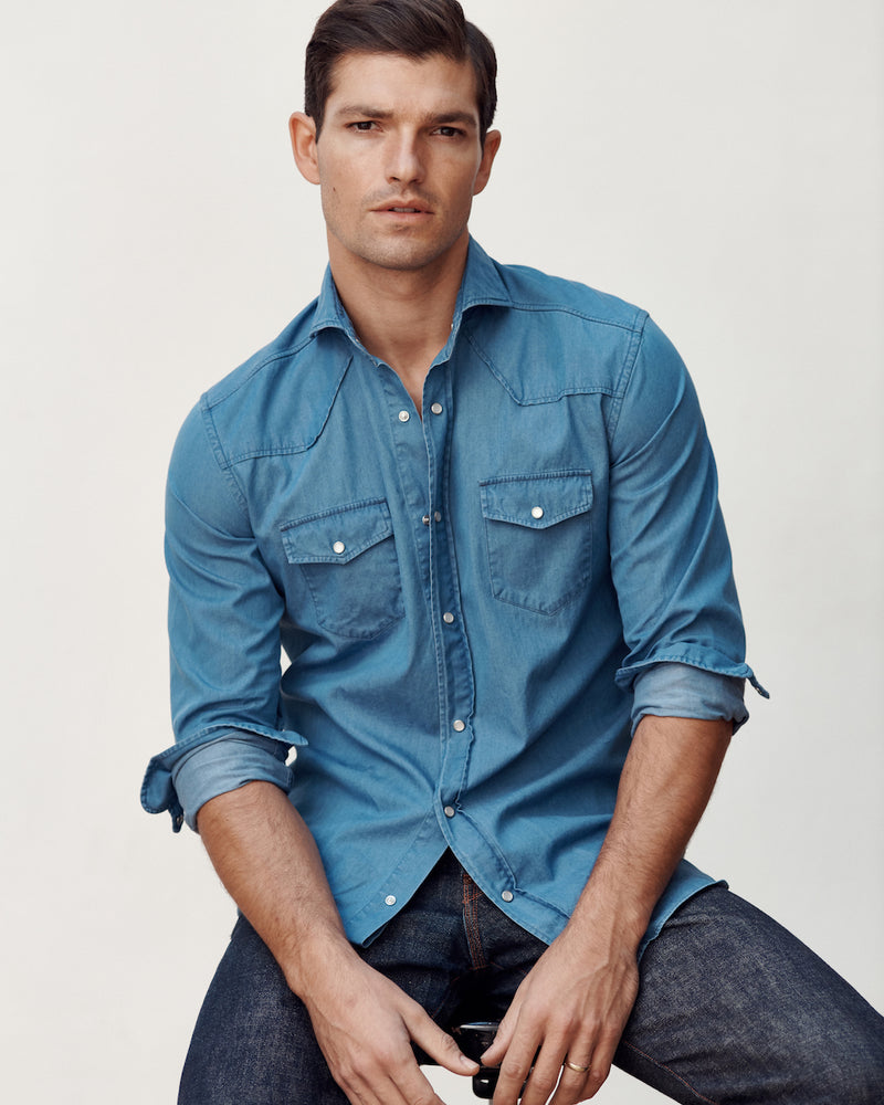Seated male model wearing the Stone Washed Denim Western Shirt and jeans.