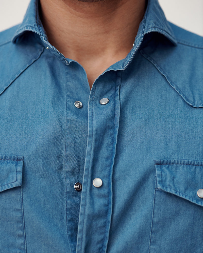 Close-up of the cutaway collar, snap buttons, and chest pockets on the Stone Washed Denim Western Shirt.