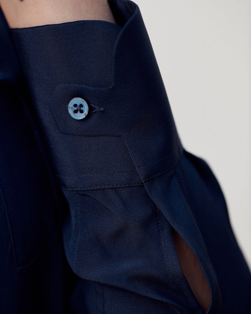 Close-up of the signature tab cuff on the navy Silk Crepe de Chine Military Shirt.