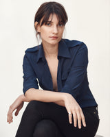Seated female model wearing the Jonathan Mezibov navy Silk Crepe de Chine Military Shirt.