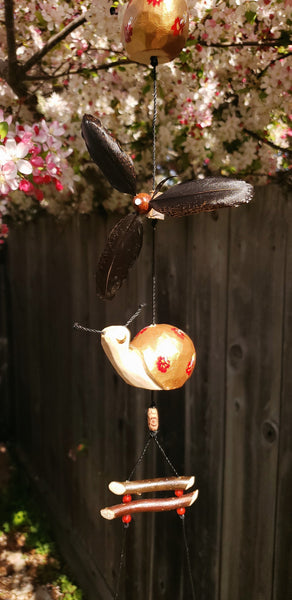 Wood craving snail painted with acrylic gold ,and weatherproof feather spinner for outdoor decor.