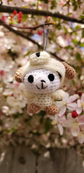 Penda bear wearing dog suite amigurumi doll . The hoodie can be pulled back but won't come off.