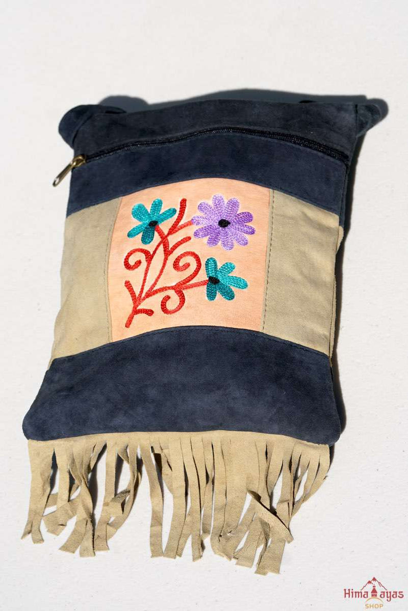 A small sling style, cross body bag with tassel/fringe at the bottom giving it a bohemian chic look.