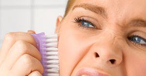 woman brushing her face with a purple brush