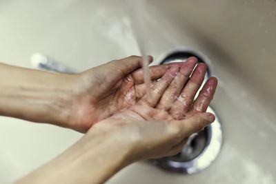 washing both hands under running water from a faucet