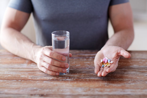 man holding vitamins on left hand and a glass of water on the right