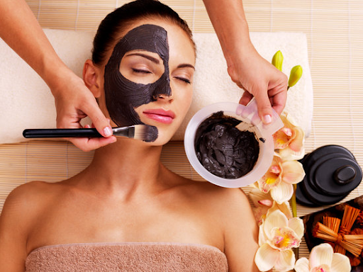 girl lying down with someone applying black mask on her face
