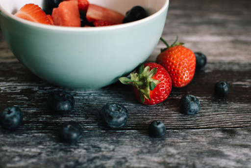 white ceramic bowl with strawberries and blueberries