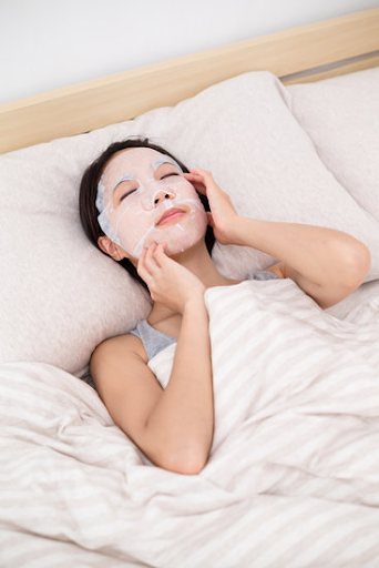 girl lying down on the bed with white sheet mask and touching her face