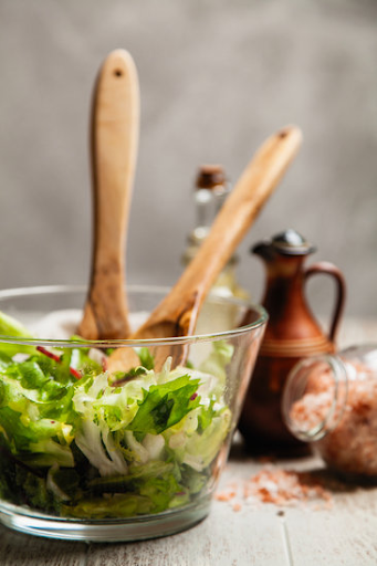 green salad in a clear bowl with two wooden mixing spoons