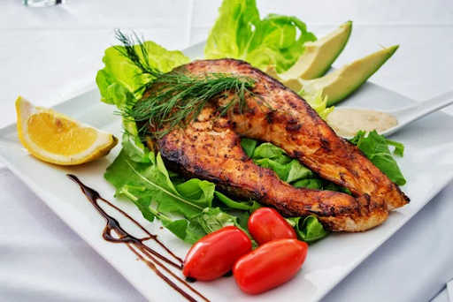 grilled salmon on a green salad with grape tomatoes, avocado and lemon on the sides