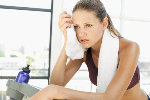 woman on exercise machine wiping sweat