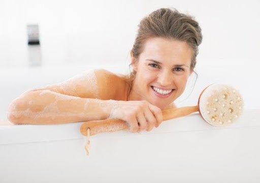 woman smiling while holding a body brush in a bathtub