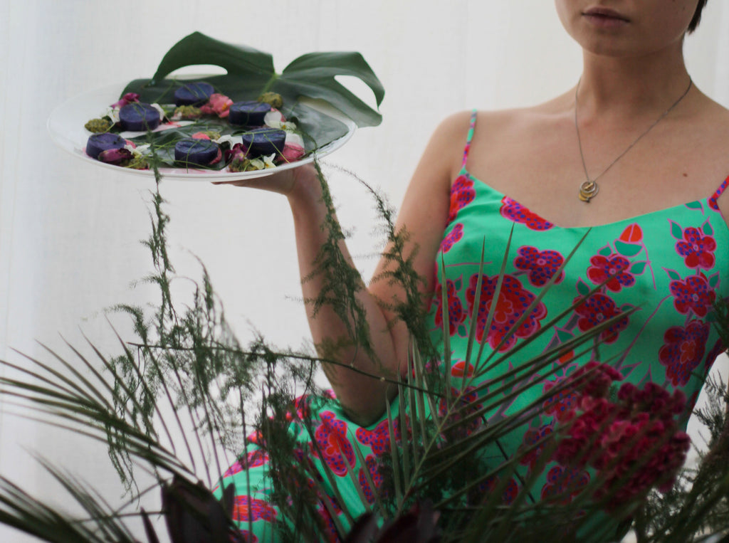 Kay Kimura-Dickson in Crimson Rose green floral print slip dress holding starter plate she designed and prepared as part of our Island Dreams collection collaboration with 0K Studios.