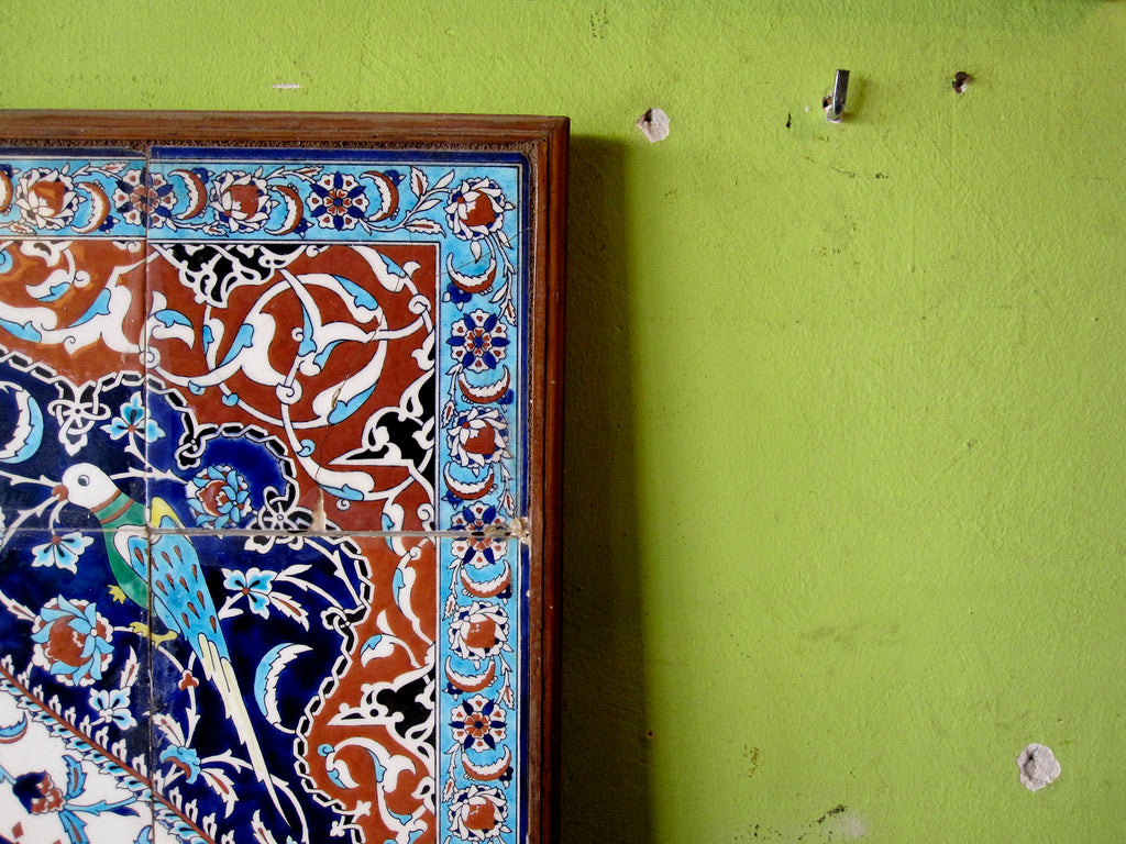 Photo of a traditional Turkish tile art in blues, white and brown with detail of a bird and flowers hung on a pistachio coloured wall.