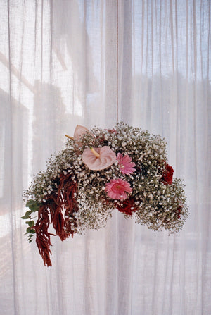 Hanging flower arrangement with pink, white, burnt red flowers in the shape of a cloud. Photography 0K Studios