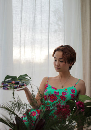 Model wearing Crimson Rose midi slip dress with green, red, pink floral print from the Island Dreams collection holding a plate with purple potatoes with feta and beetroot whip and pea, pistachio and mint pesto, garnished with pansies. Photography 0K.