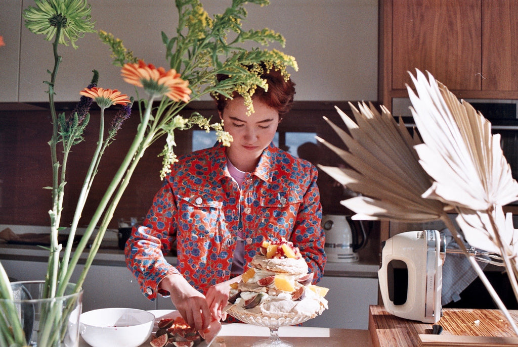 Kay Kimura-Dickinson from 0K Studios wearing Crimson Rose orange flower print cotton drill cropped jacket from the Island Dreams collection preparing a pavlova as part of our collaboration with them.
