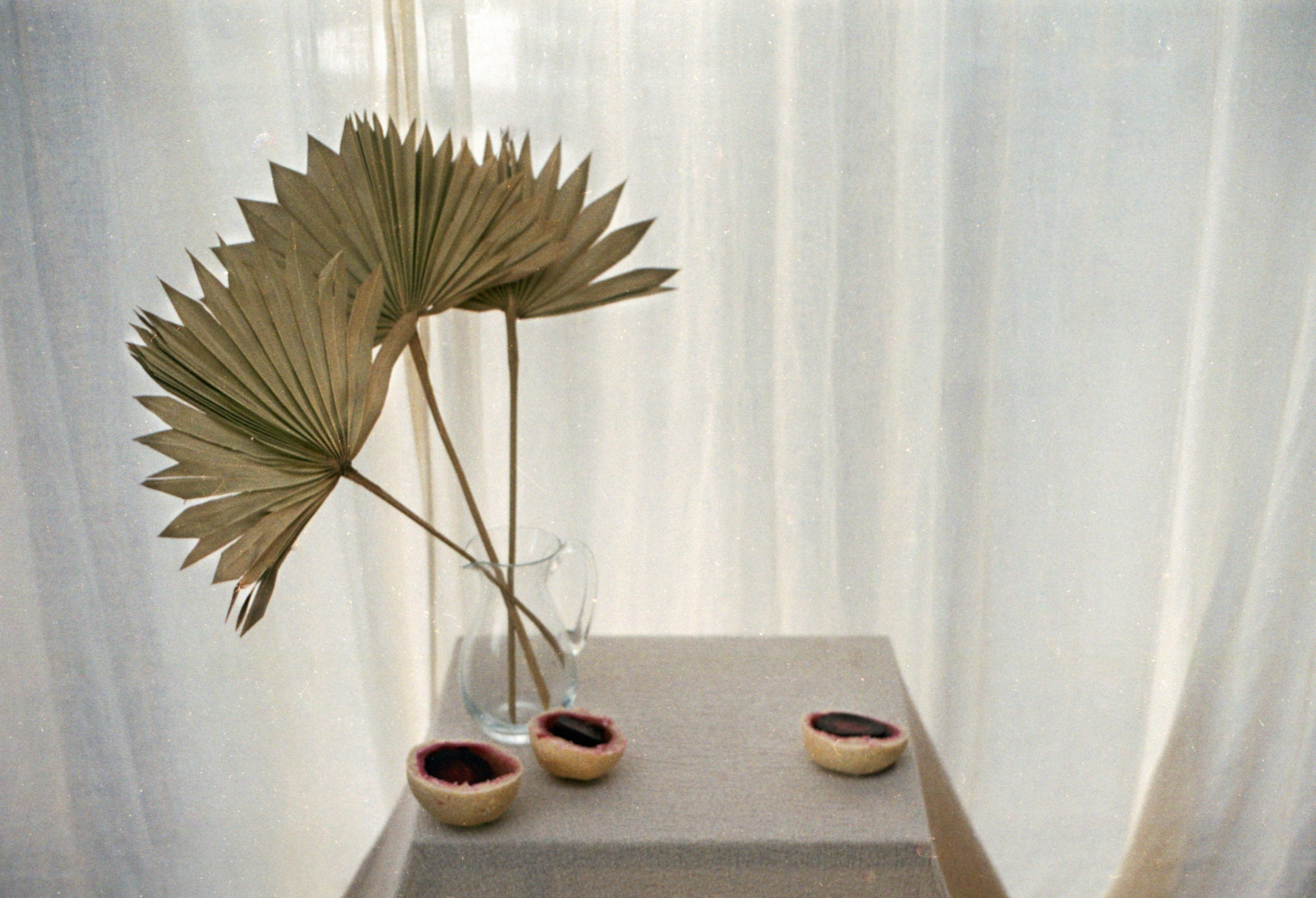 Table with pampas grass in a clear glass vase and slow roasted salt baked beetroot on a table. Photography 0K Studios.
