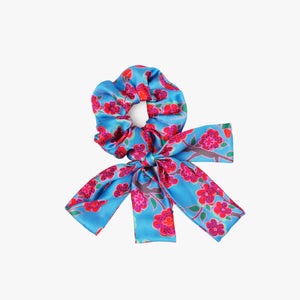 Srunchie with a bow featuring Crimson Rose hand drawn flower print from the Island Dreams collection in blue, red, pink and green.