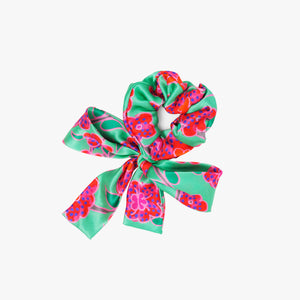 Srunchie with a bow featuring Crimson Rose hand drawn flower print from the Island Dreams collection in green, red, pink, orange and purple.
