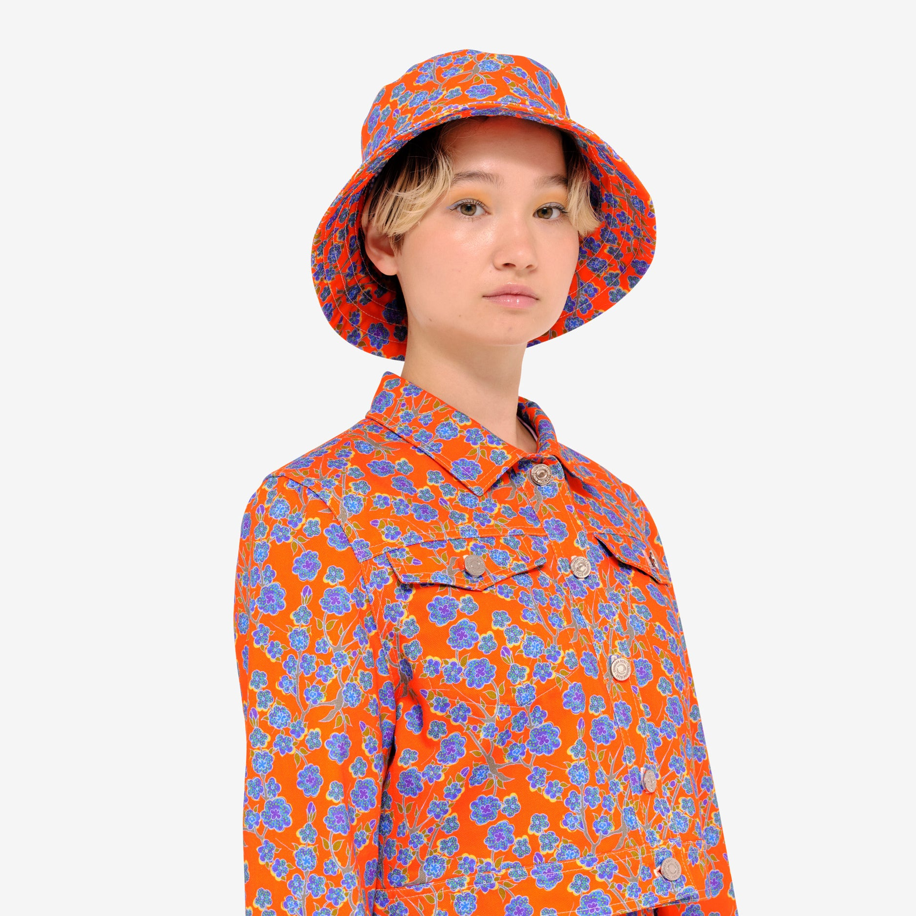 Model wearing Crimson Rose cropped cotton drill jacket and bucket hat with orange and blue floral print. Photography Rowan Corr.