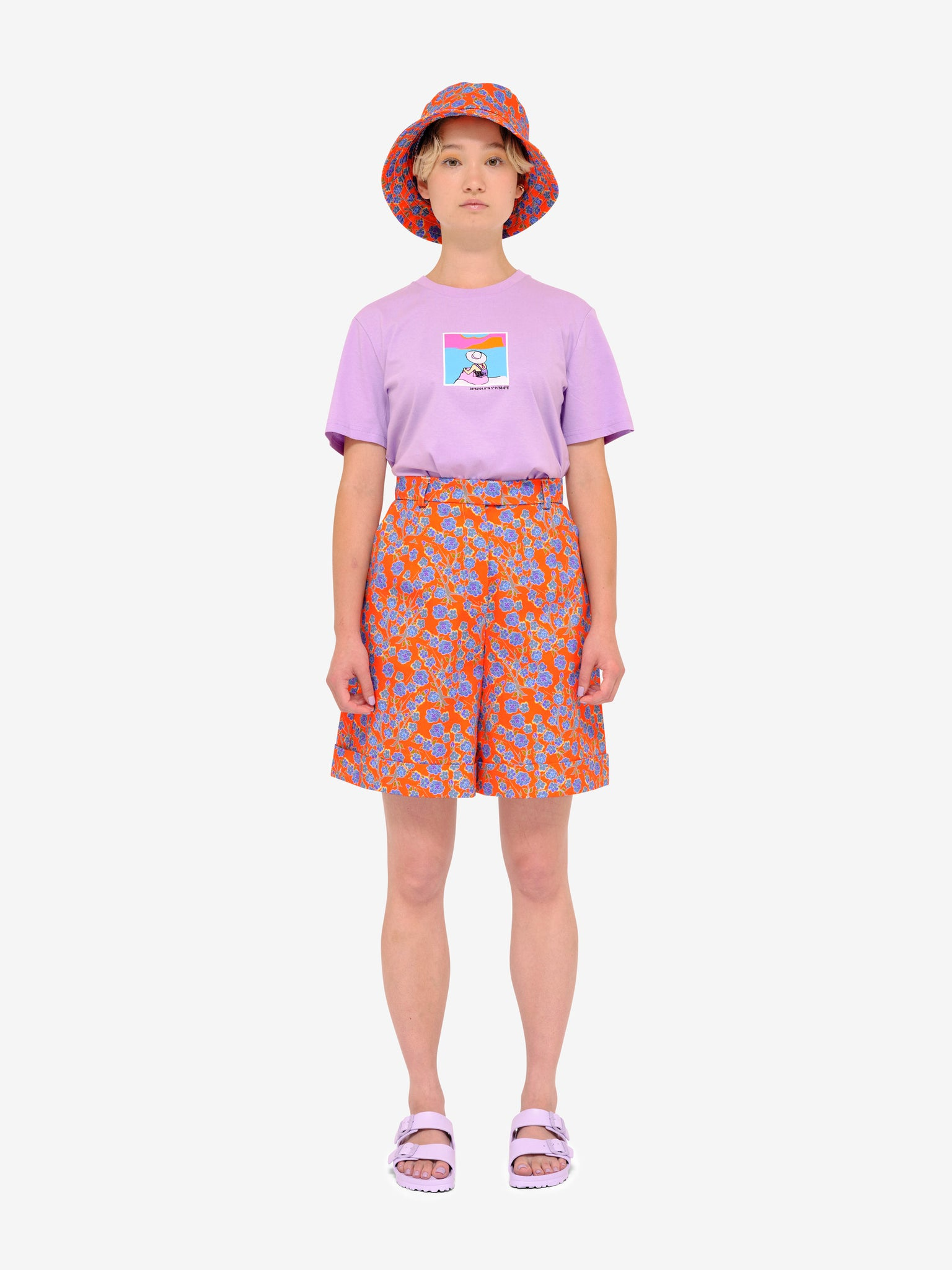 Model wearing Crimson Rose cotton drill culottes and bucket hat with orange and blue floral print, lilac Es Vedrà T-shirt and lilac sandals. Photography Rowan Corr.