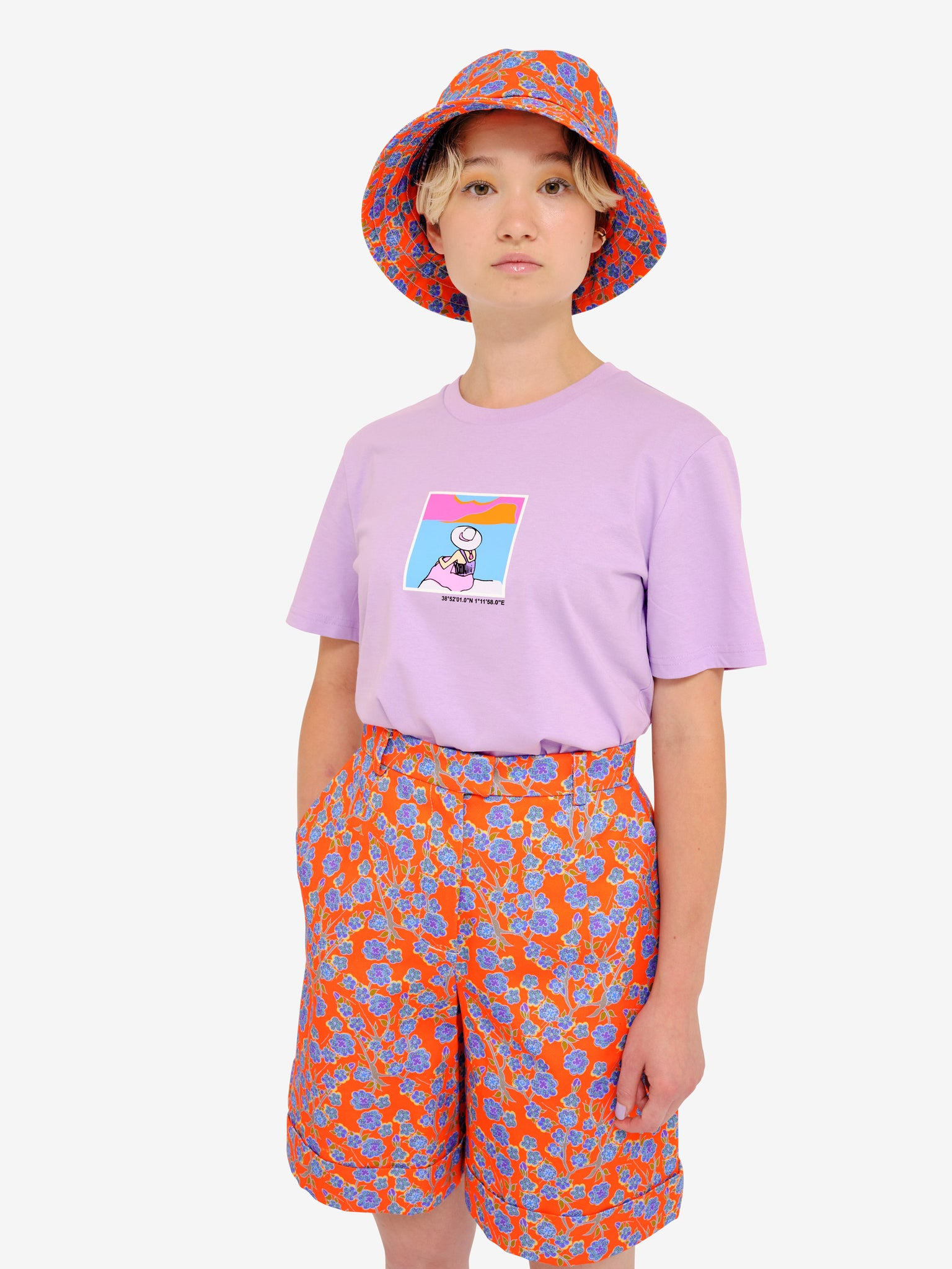 Model wearing Crimson Rose Es Vedrà lilac T-shirt, cropped cotton drill culottes and bucket hat with orange and blue floral print. Photography Rowan Corr.