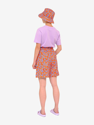 Model facing away from us wearing Crimson Rose cotton drill culottes and bucket hat with orange and blue floral print, lilac Es Vedrà T-shirt and lilac sandals. Photography Rowan Corr.