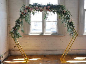 gold double hexagonal wedding arch in front of a window