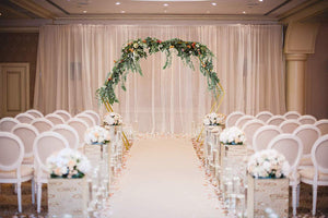 gold double hexagonal wedding arch at an indoor venue