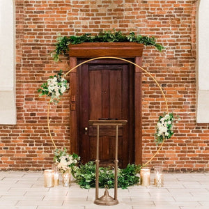 Modern Gold-Coated Round Wedding Arch in front of a brick wall and wooden door