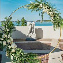Load image into Gallery viewer, Modern Gold-Coated Round Wedding Arch on a brick patio overlooking an ocean view