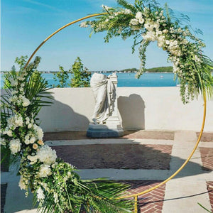 Modern Gold-Coated Round Wedding Arch on a brick patio overlooking an ocean view