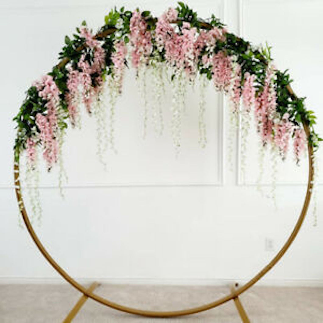 Modern Gold-Coated Round geometric Wedding Arch with pink flowers in front of a white backdrop