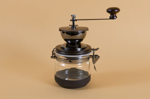 Round brown metal Coffee mill with handle, attached to a glass canister via hinge and latch with a rubber base on an orange backdorp