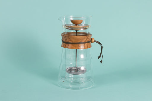 Tall double walled Coffee Server and press with metal mesh filter plunger, wooden collar handle and wooden lid on a teal backdrop