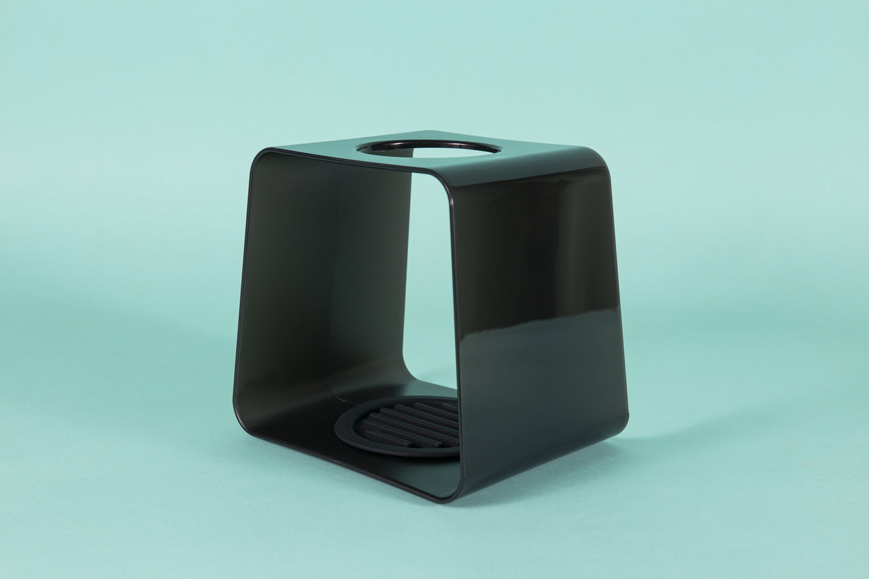 Dark black translucent plastic cube with rubber coaster at base and hole atop for dripper.