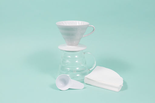 White ceramic conical coffee dripper with handle on top of an all glass coffee server with handle and plastic scoop and filter stack.