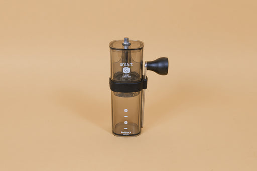 Dark clear transparent plastic coffee mill with a slim metal handle and knob attached on side