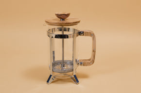 Glass french press with metal plunger and wooden lid sitting in a stainless steel basket with wooden handle.Glass french press with metal plunger and wooden lid sitting in a stainless steel basket with wooden handle.