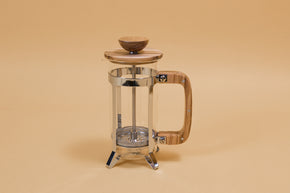 Glass french press with metal plunger and wooden lid sitting in a stainless steel basket with wooden handle.