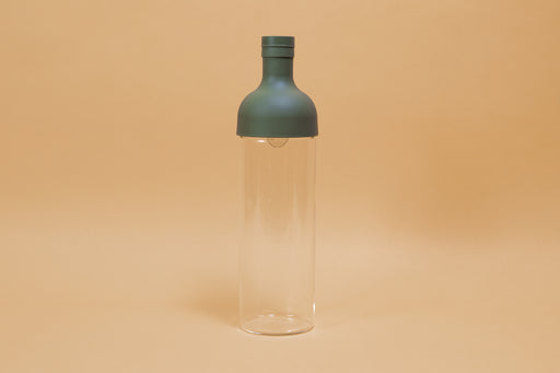 Tall glass container with green rubber wine bottle shaped top on an orange backdrop