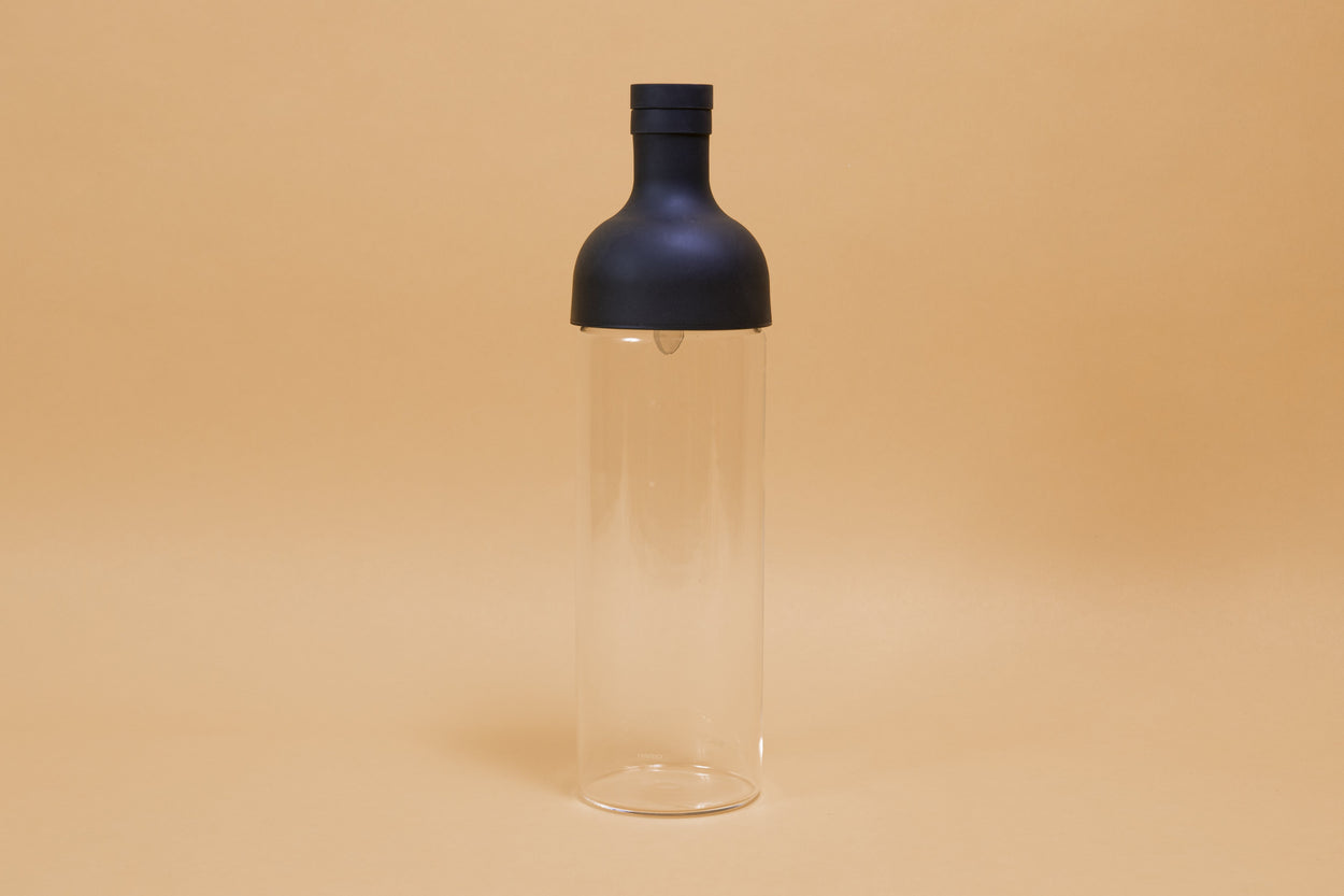 Tall glass container with black rubber wine bottle shaped top on an orange backdrop